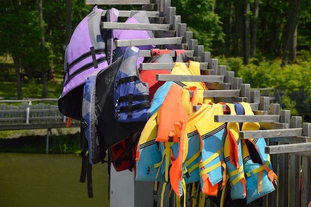 Многие спасательные жилеты висят на деревянной подставке у воды Premium Фотографии