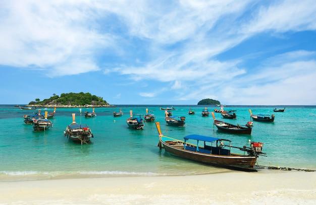 Many long-tailed boat on sunrise beach, koh lipe, thailand Premium Photo