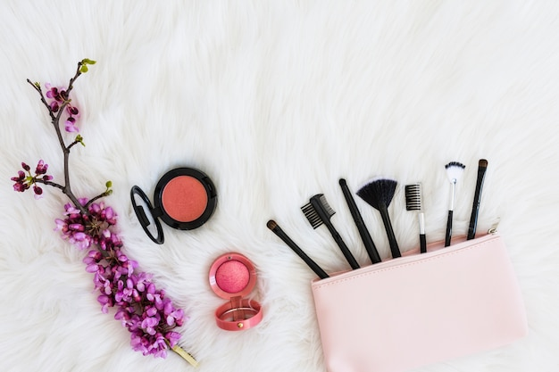 Many makeup brushes out of pink bag; flower twig and compact face powder on soft white fur Free Photo