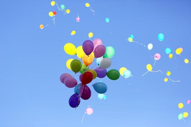 Многие разноцветные воздушные шары летают в голубом небе Premium Фотографии
