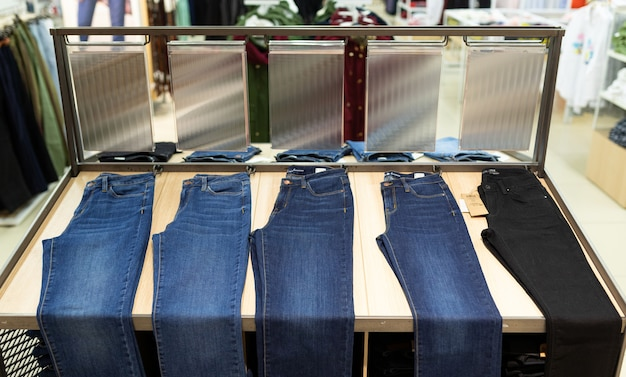 В универмаге вешают много брюк и джинсов Premium Фотографии