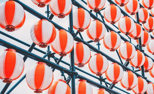 Many paper red-white oriental paper lanterns hanging in a row on blue sky Premium Photo