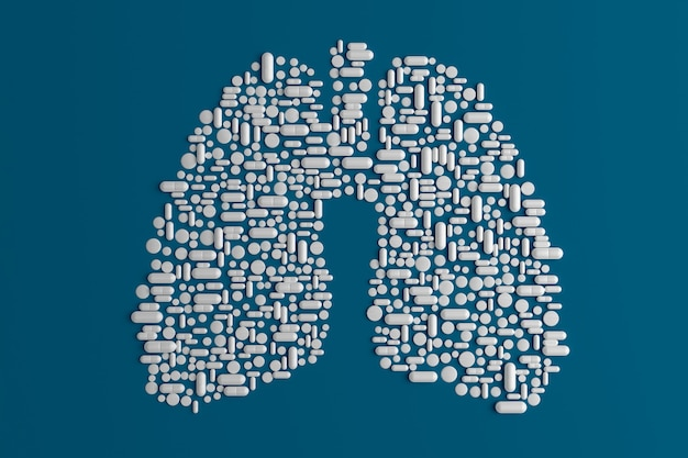 Many pills scattered on a blue in the shape of a lung Premium Photo