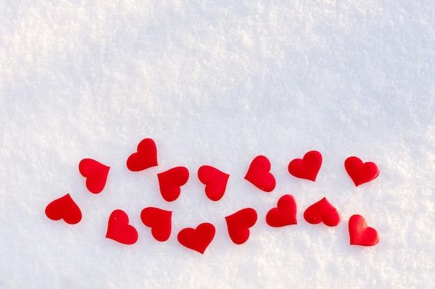 Многие красные сердца лежат на белом чистом снегу в солнечный зимний день. Premium Фотографии
