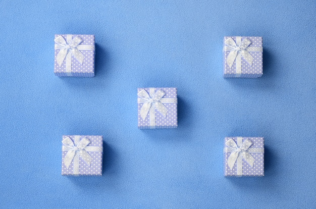 Many small gift boxes in blue color with a small bow lies on a blanket Premium Photo