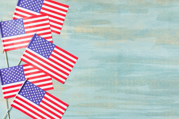 Many small usa flag on blue wooden textured backdrop Free Photo