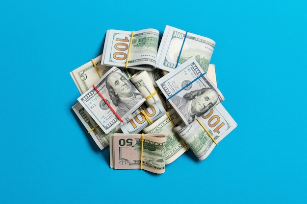 Many stack of 100 dollar bills isolated on blue Premium Photo