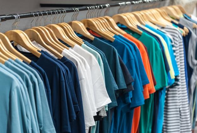 Many t-shirt hanging in a wardrobe Premium Photo