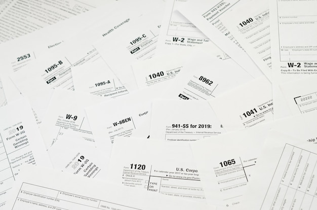 Many tax form blanks lies on table close up. tax payers paperwork routine and bureaucracy concept Premium Photo