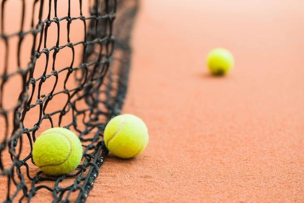 Many tennis balls on net Free Photo