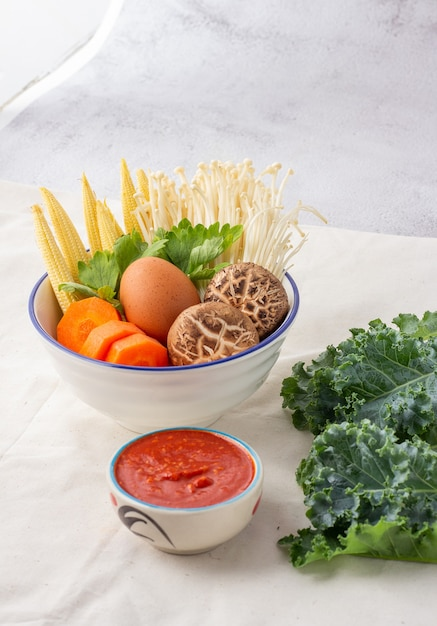 흰 그릇에 담긴 많은 야채에는 당근, 아기 옥수수, 표고 버섯, 황금 바늘, 셀러리 및 닭고기 달걀이 포함됩니다. 스키야키 세트와 소스. 프리미엄 사진