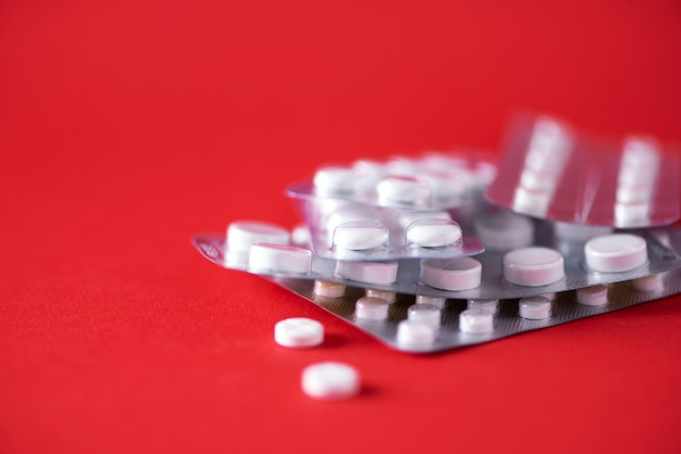 Много белая капсула в пакете волдыря на красной предпосылке. копировать пространство куча лекарств, лечение простуды. Premium Фотографии