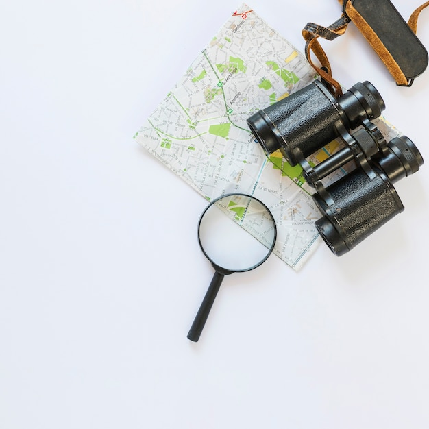 Map; binoculars and magnifying glass on white surface Free Photo