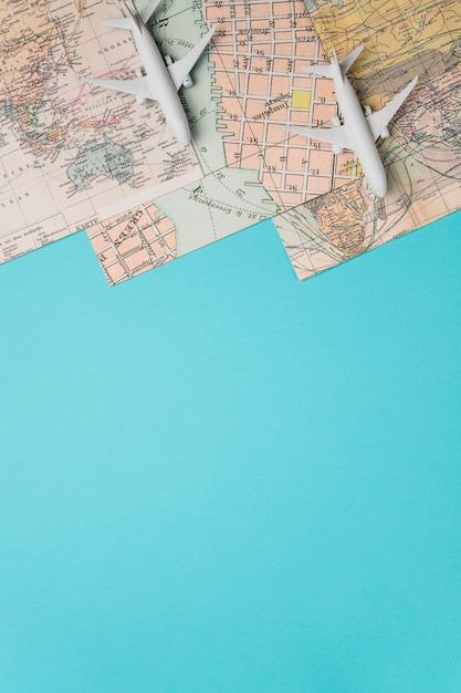 Maps and toy planes on blue background Free Photo
