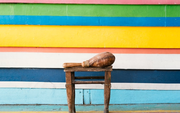 Maraca alongside vibrant wall in stripes with copy-space Free Photo