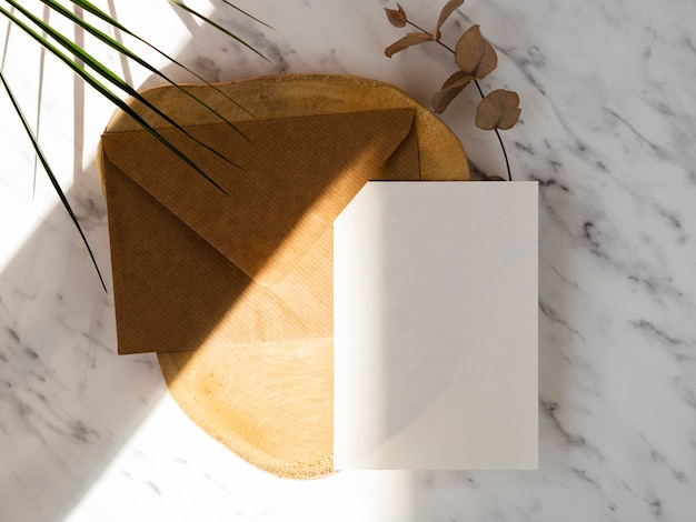 Marble background with a wooden plate with a brown envelope and a white blank Free Photo