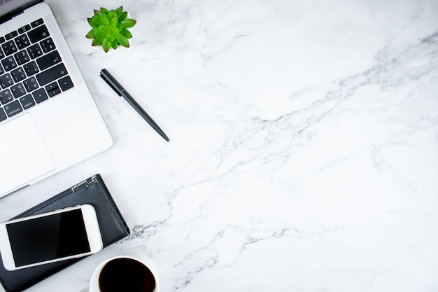 Marble desk with laptop, coffee and accessories Premium Photo