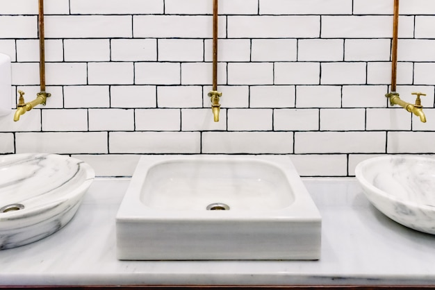 Marble sink in a public restroom with retro golden water tap with copper pipes on wall Premium Photo