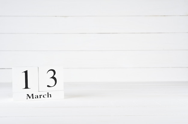 March 13th, day 13 of month, birthday, anniversary, wooden block calendar on white wooden background with copy space for text. Premium Photo