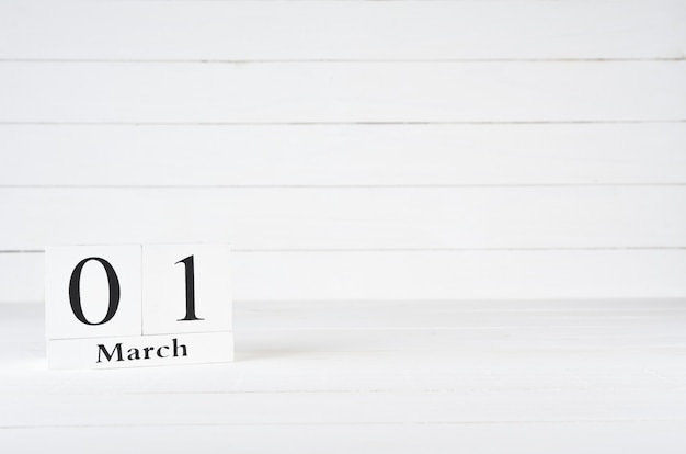 March 1st, day 1 of month, birthday, anniversary, wooden block calendar on white wooden background with copy space for text. Premium Photo