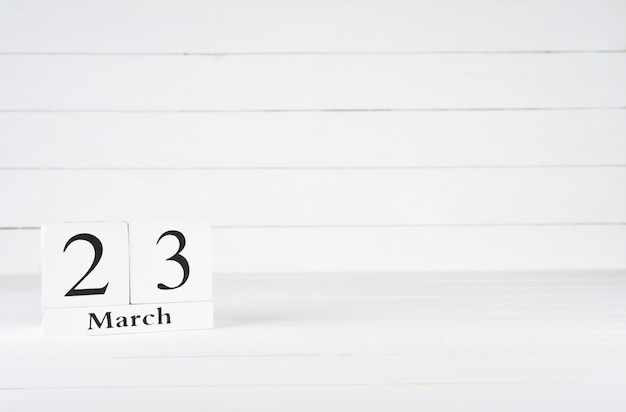 March 23rd, day 23 of month, birthday, anniversary, wooden block calendar on white wooden background with copy space for text. Premium Photo