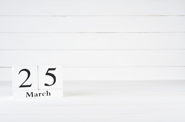 March 25th, day 25 of month, birthday, anniversary, wooden block calendar on white wooden background with copy space for text. Premium Photo