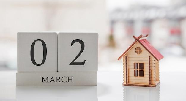 3月のカレンダーとおもちゃの家。月の2日目。印刷のためのハードメッセージまたは記憶 Premium写真