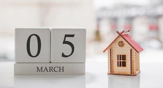 3月のカレンダーとおもちゃの家。月の5日目。印刷のためのハードメッセージまたは記憶 Premium写真