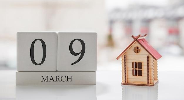 3月のカレンダーとおもちゃの家。月の9日目。印刷のためのハードメッセージまたは記憶 Premium写真