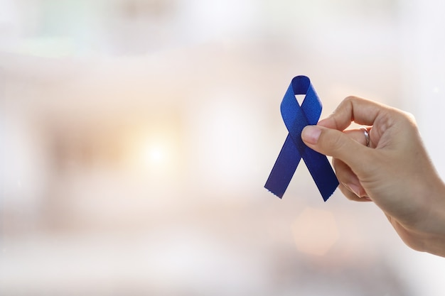 Premium Photo March Colorectal Cancer Awareness Month Man Holding Dark Blue Ribbon For Supporting People Living And Illness Healthcare Hope And World Cancer Day Concept