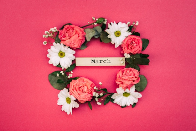 March text inside white flowers and leaf decorated on red backdrop Free Photo