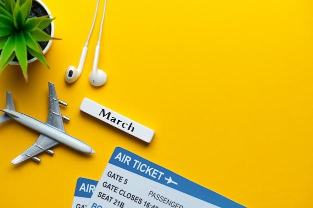 3月の休暇のコンセプト-黄色の壁のチケットとおもちゃの飛行機。コピースペース Premium写真