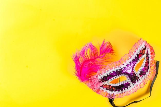 Mardi gras background with holiday mask on bright yellow background Premium Photo