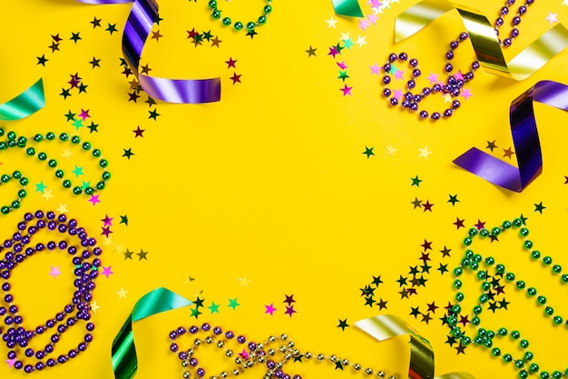Mardi gras carnival concept - beads on yellow background, top view Premium Photo