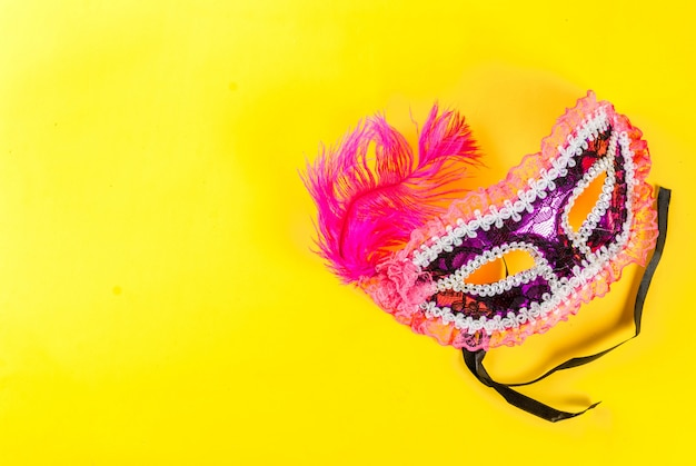 Mardi gras  with holiday mask, on bright yellow    copyspace top view Premium Photo