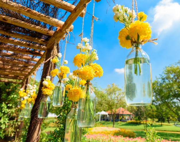 The marigold flowers in a glass bottle hanging. flower vase arrangements Premium Photo