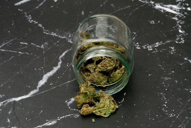 Марихуана, конопля лекарственная, травка суставная, в стеклянной таре, лекарства. Premium Фотографии
