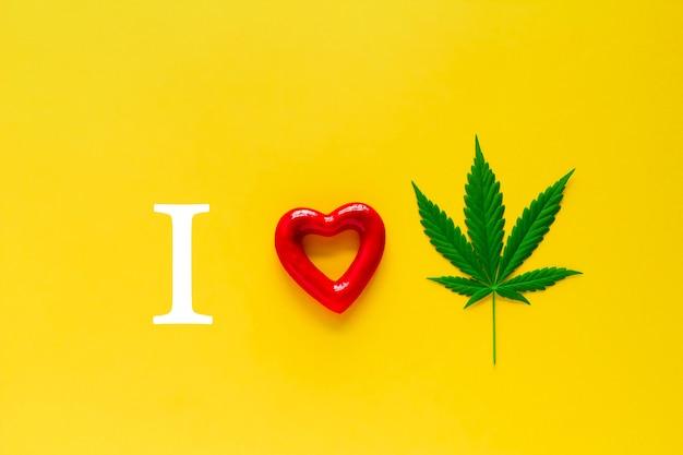Marijuana and red heart on a yellow background, Premium Photo
