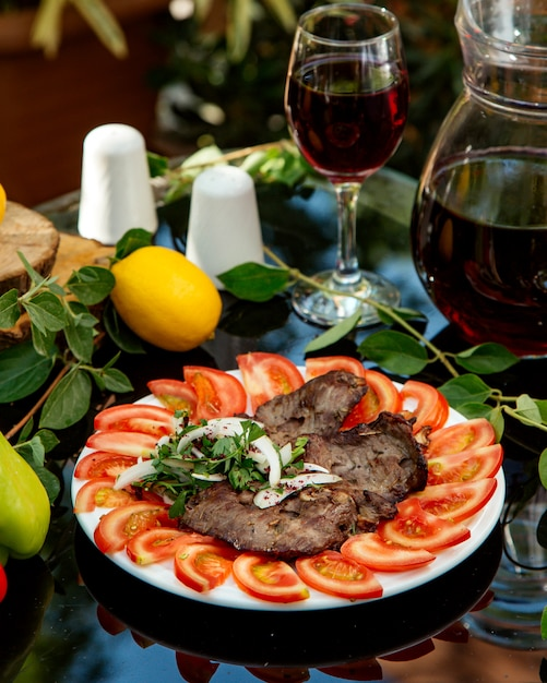 Marinated beef served with tomato slices, onion and coriander Free Photo