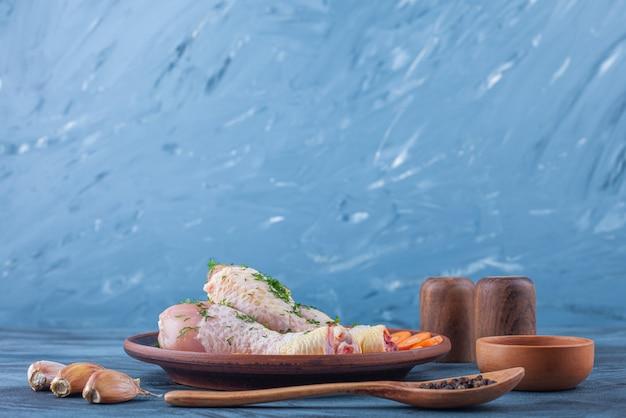 파란색 표면에 향신료, 숟가락, 마늘 옆에 나무 접시에 절인 나지만, 얇게 썬 당근 무료 사진