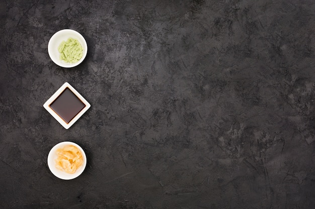 Marinated ginger; soy sauce and wasabi bowl arranged in row over textured black surface Free Photo