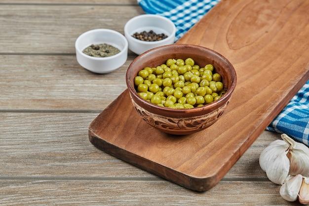 木製のカップでマリネしたグリーンピース豆。 無料写真