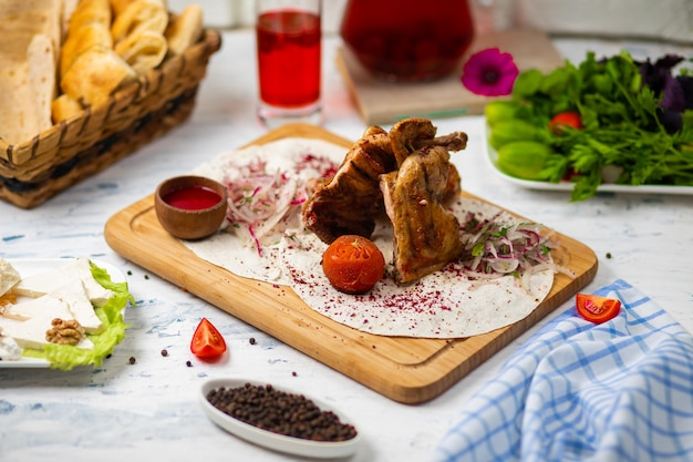 Marinated grilled healthy chicken breasts cooked on a summer bbq and served in lavash with fresh herbs, wine, bread on a wooden board, close up view Free Photo