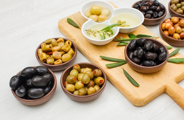 Marinated olives and olive oil with olive leaves in a bowls and cutting board on white wood, high angle view. Free Photo