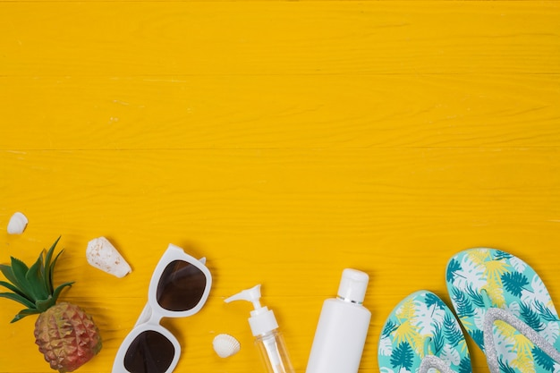 Marine travel , sunblock creams, slippers and pineapples placed on a yellow wooden floor. Free Photo