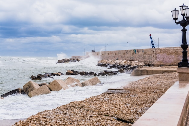 Maritime walk hit by the waves of a marine storm and the strong wind. Premium Photo
