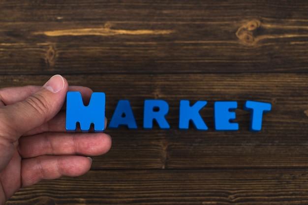 Рука и палец располагают текстовые буквы слова market на деревянной таблице, с копией пространства для добавления рекламного слова или продукта. Premium Фотографии
