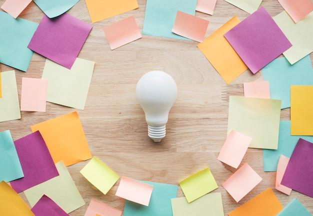 Концепции идей маркетинга, планирования с белой лампочкой и красочной записной книжкой на деревянном столе. никто Premium Фотографии