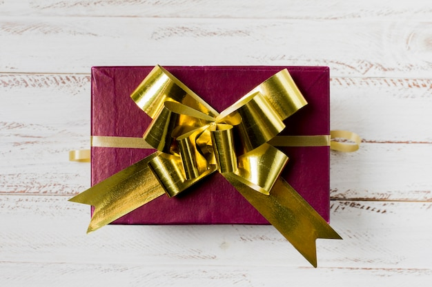 Maroon gift box with golden ribbon over wooden desk Free Photo