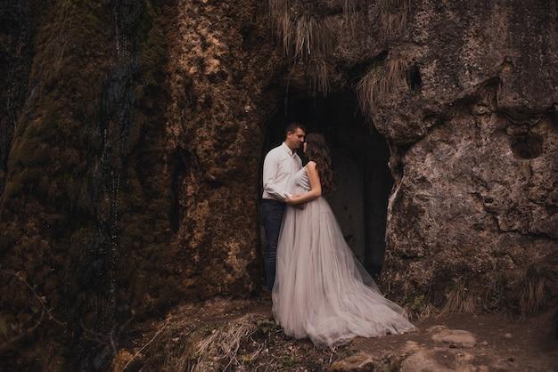 Супружеская пара мужчина с беременной женщиной с большим животом на природе у горы Premium Фотографии